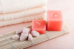 Peach spa concept. Peach color spa setting with red candles and towel Royalty Free Stock Photos