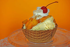 Peach Sundae. Fresh peaches and ice cream in a waffle bowl royalty free stock images
