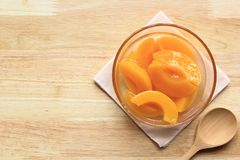 Peach in syrup and wooden spoon on table background royalty free stock images