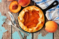 Peach tart in cast iron skillet over rustic wood background Royalty Free Stock Photography