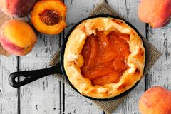 Peach tart in cast iron skillet, overhead on white wood Royalty Free Stock Photos