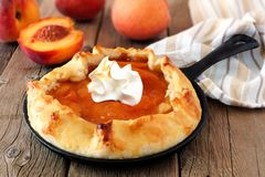 Peach tart with whipped cream in cast iron baking skillet Royalty Free Stock Images