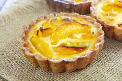 Peach tartlet individual pastry. On a wooden surface royalty free stock photography