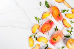 Peach tea popsicles. Summer desserts. Frozen drinks. Sweet fruit popsicles from frozen peach tea with mint. On a white marble table, with ingredients - peaches Stock Photo