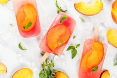 Peach tea popsicles. Summer desserts. Frozen drinks. Sweet fruit popsicles from frozen peach tea with mint. On a white marble table, with ingredients - peaches Stock Photos