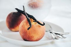 Peach and vanilla pod as food ingredients for dessert cooking. stock image