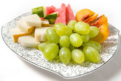 Peach, white grape, watermelon and melon on the plate. On white background Royalty Free Stock Photo