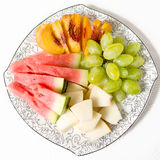 Peach, white grape, watermelon and melon on the plate. On white background Royalty Free Stock Photos
