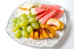 Peach, white grape, watermelon and melon on the plate. On white background Stock Image