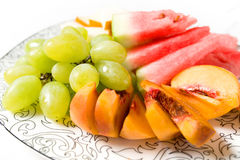 Peach, white grape, watermelon and melon on the plate. On white background Stock Photography