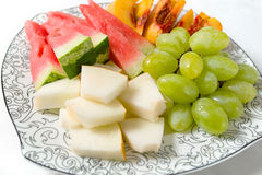 Peach, white grape, watermelon and melon on the plate Royalty Free Stock Image