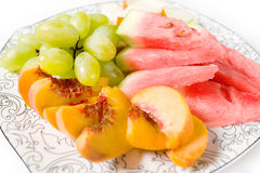 Peach, white grape, watermelon and melon on the plate. On white background Stock Images