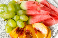 Peach, white grape, watermelon and melon on the plate. On white background Royalty Free Stock Image