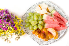Peach, white grape, watermelon, melon on the plate and dried flowers. On white background Stock Photo