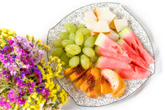 Peach, white grape, watermelon, melon on the plate and dried flowers. On white background Stock Images