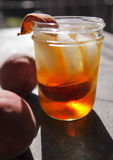 Peache grilling ice tea. Ice tea spiked with bourbon and grilled peaches served in an old-fashioned jar type glass a great thirst quencher on a hot June Summer Royalty Free Stock Images