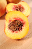 Peaches. Peach and half a peach cut to reveal the stone Royalty Free Stock Image
