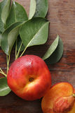 Peaches. Peaches with leaves on a wooden board Royalty Free Stock Photography