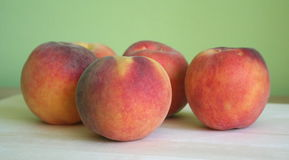 Peaches. Some peaches with green background Royalty Free Stock Photography