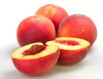 Peaches. Three peach and peach cut in half on white background Royalty Free Stock Images