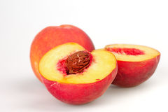Peaches. Peach and the two halves of a peach on white background royalty free stock image