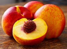 Peaches. Halved peach and other whole peaches on the table Royalty Free Stock Photo