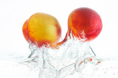 Peaches. Two peaches jumping out of the water Royalty Free Stock Photos