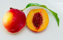 Peaches. One and a half peach with pit and leaf Royalty Free Stock Images
