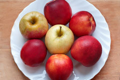 Peaches and apples on a white round plate Stock Image