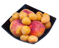 Peaches and apricots in black plate Royalty Free Stock Images