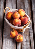 Peaches in basket on old wooden table. Peaches in knitted basket on old rustic white wooden table and dark background Royalty Free Stock Image