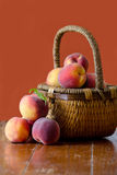 Peaches and basket on rust colored background Stock Photo