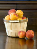 Peaches in Basket 2. A wooden basket filled with fresh ripe peaches on dark wood table and antique sideboard in background royalty free stock photos
