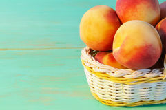 Peaches in basket on wooden background Stock Photos
