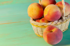 Peaches in basket on wooden background Royalty Free Stock Photography