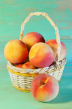 Peaches in basket on wooden background Royalty Free Stock Photo