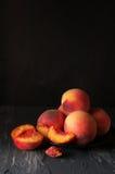 Peaches on black Stock Photos