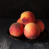 Peaches on black Stock Photo