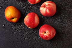Peaches on a black table in drops Stock Image