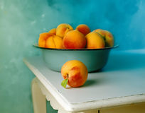 Peaches in blue old bowl. Group of Peaches in blue old bowl and one peach on the white old table Stock Photos