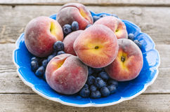 Peaches and blueberries in the blue plate Stock Photography