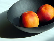 Peaches in a bowl. Two peaches in a black bowl Stock Images