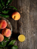 Peaches on a branch with leaves on a vintage metal plate, a glass of juice on a dark wooden background,  top view Royalty Free Stock Image