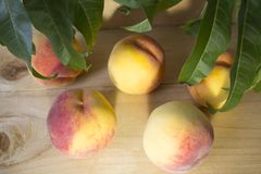Peaches on a brown background. peaches with green leaves. view from above in green leaves. Royalty Free Stock Photo
