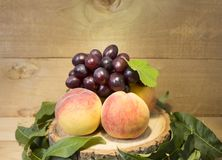 Peaches on a brown background. peaches with green leaves. view from above in green leaves. peaches with dark blue grapes. Royalty Free Stock Image