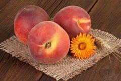 Peaches on burlap background. Ripe peaches on jute fabric background Stock Photos