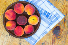 Peaches in a ceramic plate. Napkin in the blue-white grid Royalty Free Stock Image