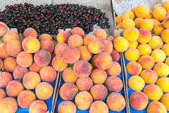Peaches and cherries for sale at a market Royalty Free Stock Image