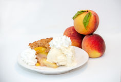 Peaches and cobbler on white. Home made peach cobbler with ice cream and whipped cream, on a white back ground with peaches royalty free stock image