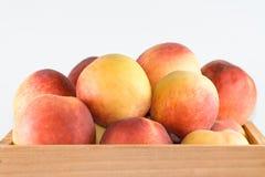 Peaches in crate. Stock Photos